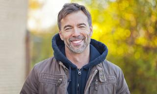 standing man smiling with bright smile I dental implants in moline il