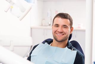 man in dental exam chair smiling I dentist in moline il