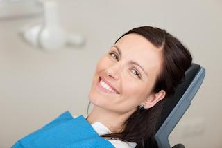 woman laying on dental exam chair smiling I digital dentistry in moline il