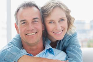 middle-aged couple facing forward smiling I restorative dentistry in moline il