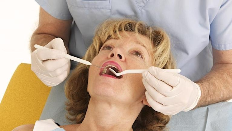 Woman receiving dental exam at Moline IL dentist office